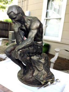 Rodin's The Thinker, polished bronze, with an alternate head/face.